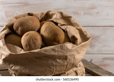 Organically grown potatoes in a paper bagon top of a wooden crate with white wooden board background