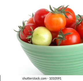 Organically grown tomatos in a green bowl isolated on a white background. One green tomato in the group.