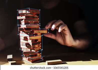 organization ideas concept with hand pull out block of wooden piece from stack strategy and risk concept