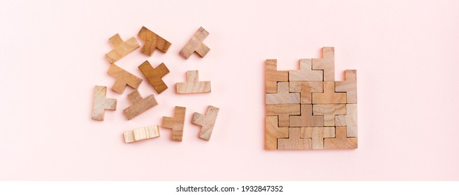 Organization and order. Wooden puzzle pieces are stacked correctly and chaotically scattered in disarray on a pink background. Web banner