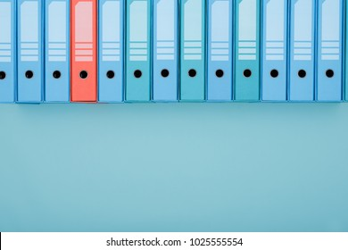 Organized archive with ring binders in a row, one is red: archive, database and search concept