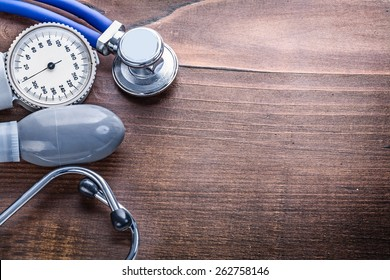 organized copyspace blood pressure monitor stethoscope on vintage wooden board medical concept