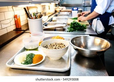 An organized prep kitchen with male in chef's coat and blue apron chopping greens with bowls of collard greens, herbs, spices and garlic on metal tray in the foreground.