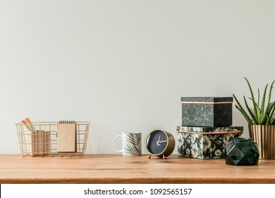 Organized table top with floral boxes, mug, clock and metal box on an empty wall
