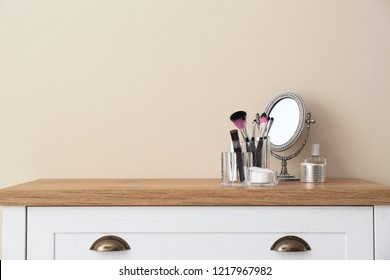 Organizer with makeup cosmetic products and mirror on table against light wall. Space for text