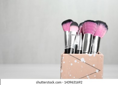 Organizer with professional makeup brushes against light background. Space for text