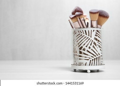 Organizer with professional makeup brushes on light table. Space for text
