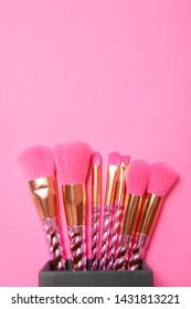 Organizer with set of makeup brushes on pink background, top view. Space for text
