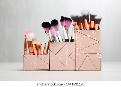 Organizers with professional makeup brushes on light table