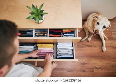 Organisation und Reinigung des Hauses. Mann, der ordentliche gefaltete T-Shirts in Schublade vorbereitet.
