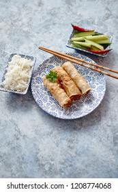 Orginal asian deep fried spring rolls placed on beautiful oriental style plate with chopstick, boiled rice, cucomber nad hot chilli peppers od side. Top view on stone background.