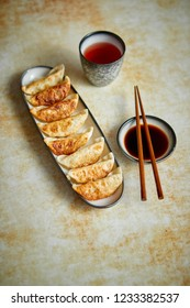 Orginal asian dumplings gyoza served in long plate with soy souce in a bowl and a cup of tea. With chopsticks. Placed on rusty background.