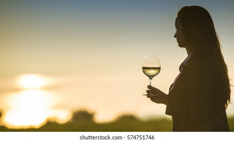 Oriahovo, Bulgaria - September 17, 2015 : Woman drinking wine, watching the sunset over Danube river