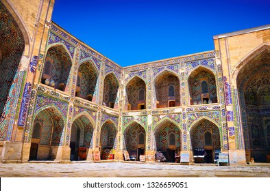 Orient inner courtyard with beautiful arch portals decorated with glazed tile, blue sky and souvenir shops in Sher-Dor Madrasah, Registan square, Samarkand (Samarqand), Uzbekistan, Central Asia