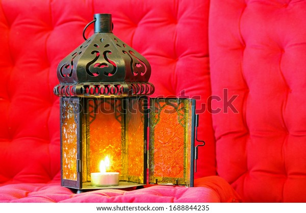 Oriental aladdin lamp with candle pink background