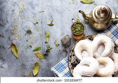Oriental Algerian sweet cookies( gazelle horns cookies ), tea cup and pot  and mint leaves