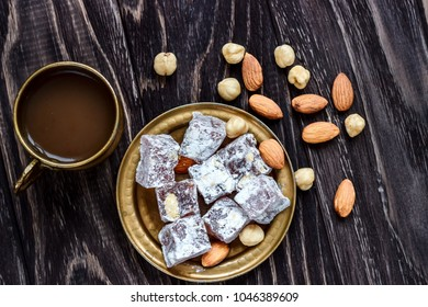 Oriental Arabian sweets with different nuts a cup of coffee. Eastern sweets. Traditional Turkish delight (Rahat lokum) on a wooden background. View from above.