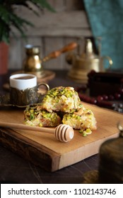 """oriental Arabic sweet called """"Basbosa"""" it is semolina and coconut cake with sugar syrup on wooden board and a cup of coffee on the background,"""