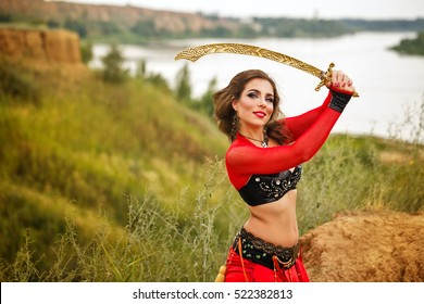 Oriental Beauty dance with a sword. Tribal style. Nice girl in national dress dancing in the open air. Nomads.