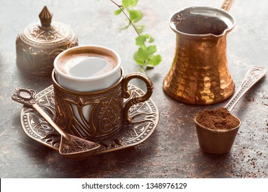 Oriental coffee cooked in traditional Turkish copper coffee pot poured in a cup on a dark table