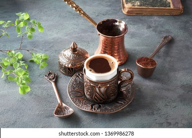 Oriental coffee cooked in traditional Turkish copper coffee pot and  served in a matching cup in ornate metal cup holder