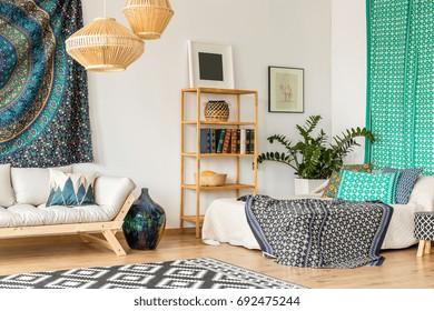 Oriental design in small studio interior with wooden furniture