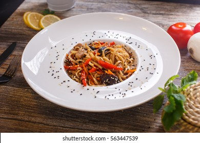 Oriental dishes - udon noodles with mushrooms and peppers