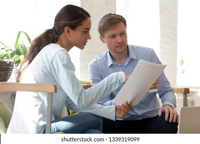 Oriental female showing papers to caucasian male. Student presents course work to teacher. Business people discuss new project. Man and woman reading contract. People at work concept. Office routine