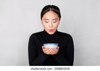 Una chica oriental vestida de negro sopla la comida dentro de su tazón chino.