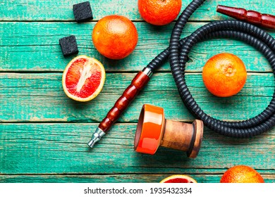 Oriental smoking hookah or shisha with tobacco with grapefruit flavor.Modern fruit shisha with orange