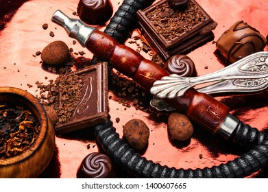 Oriental smoking hookah with a taste of chocolates. Chocolate tobacco flavor.Modern hookah with chocolate