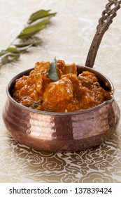 Oriental stew, butter chicken, with curry leaves,in a copper pot,  on gold background.
