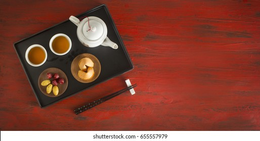 Oriental style Chinese afternoon tea set with snack served on rustic red background. Horizontal banner format text space image.