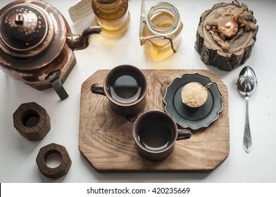 Oriental style tea serving with brown sugar, honey and herbal infusions in the bottles. Wooden board, white rustic table. Top view.