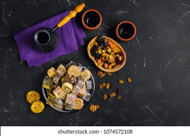 Oriental Sweets. Assorted traditional turkish delight Rahat lokum on black stone background. Dried fruit figs, raisins, prunes, nuts. Coffee, Turk, cups. Top view.