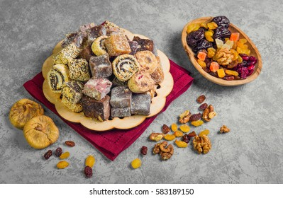 Oriental Sweets. Assorted traditional turkish delight Rahat lokum on gray stone background. Rahat Lukum (lokum) sprinkled with coconut, sugar and sesame. Dried fruit figs, raisins, prunes, nuts.