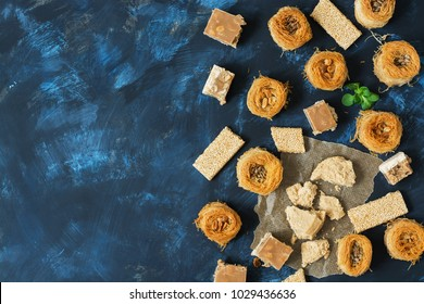 Oriental sweets, baklava, halva, sesame with honey, sherbet on a blue background. Top view, space for text