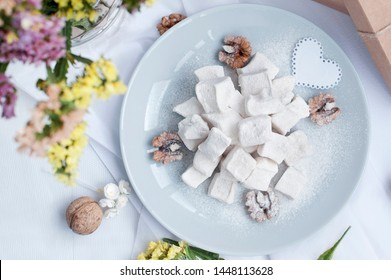 Oriental sweets lie on a round plate on the table. Sweet, beautifully stacked pyramid and crushed with sweet powder, walnuts around lay. On the table there is a gift box and flowers.