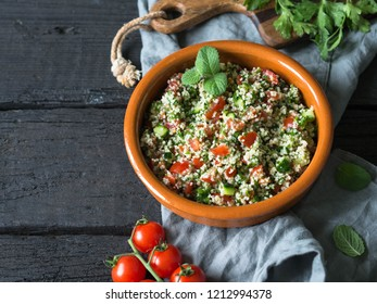 Oriental tabbouleh salad with couscous, vegetables and herbs in a brown bowl on a dark wood background