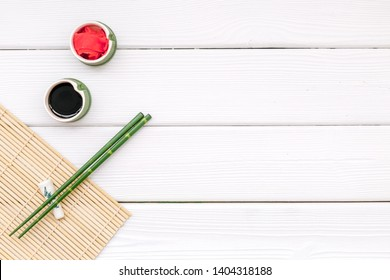 oriental table set up with bamboo sticks for sushi and maki, soy sauce white wooden background top view space for text