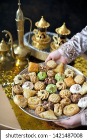 Oriental tea tray and cookies symbolising Moroccan hospitality, Islamic holidays food with decoration. Ramadan kareem. Eid mubarak. Oriental hospitality concept. Tea glasses and pot, traditional delig