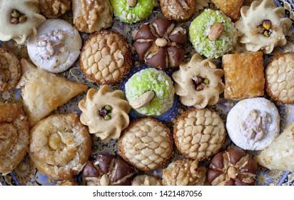 Oriental tea tray and cookies symbolising Moroccan hospitality, Islamic holidays food with decoration. Ramadan kareem. Eid mubarak. Oriental hospitality concept. Tea glasses and pot, traditional delig