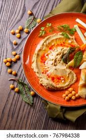 Oriental traditional hummus sauce with fresh vegetables on plate. Restaurant menu.