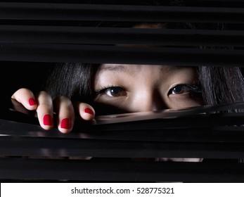 Oriental woman, behind a blind