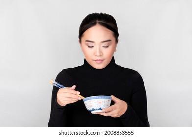 Mujer oriental comiendo comida en un bol con un palo