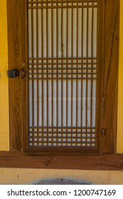 Oriental Wooden Slatted Door Of Old Stucco Building With Rice Paper Used  For Privacy On Inside