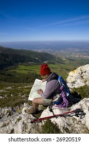 Orienteering - A trekker consulting a map, alone on a mountain, over a clear blue sky