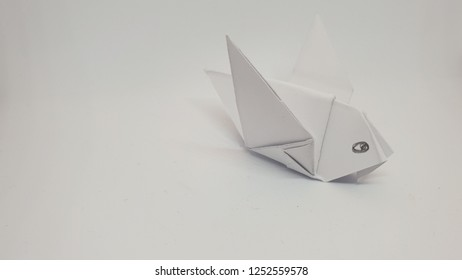 origami bird from white paper studio closeup isolated