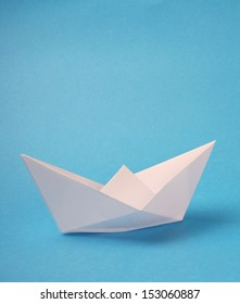 An origami boat made from blank white paper on a blue background with copy space