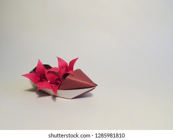origami boat sampan with red lilies on white background
